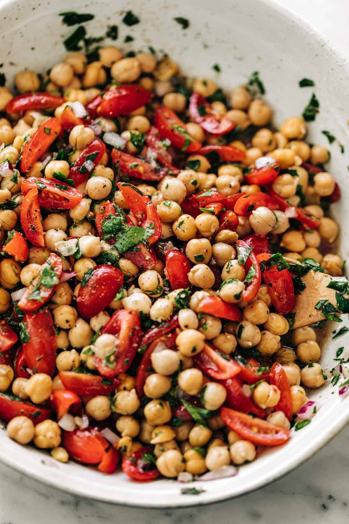 Chickpea Tomato Salad mixed with a lemon herb dressing in a white bowl on a white marble table background | cafedelites