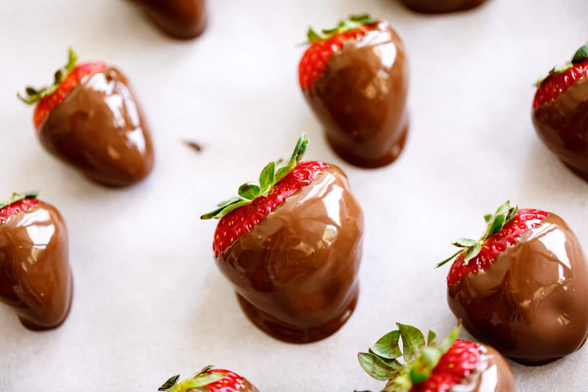 Strawberries on a baking sheet lined with baking paper with fresh chocolate dipped strawberries