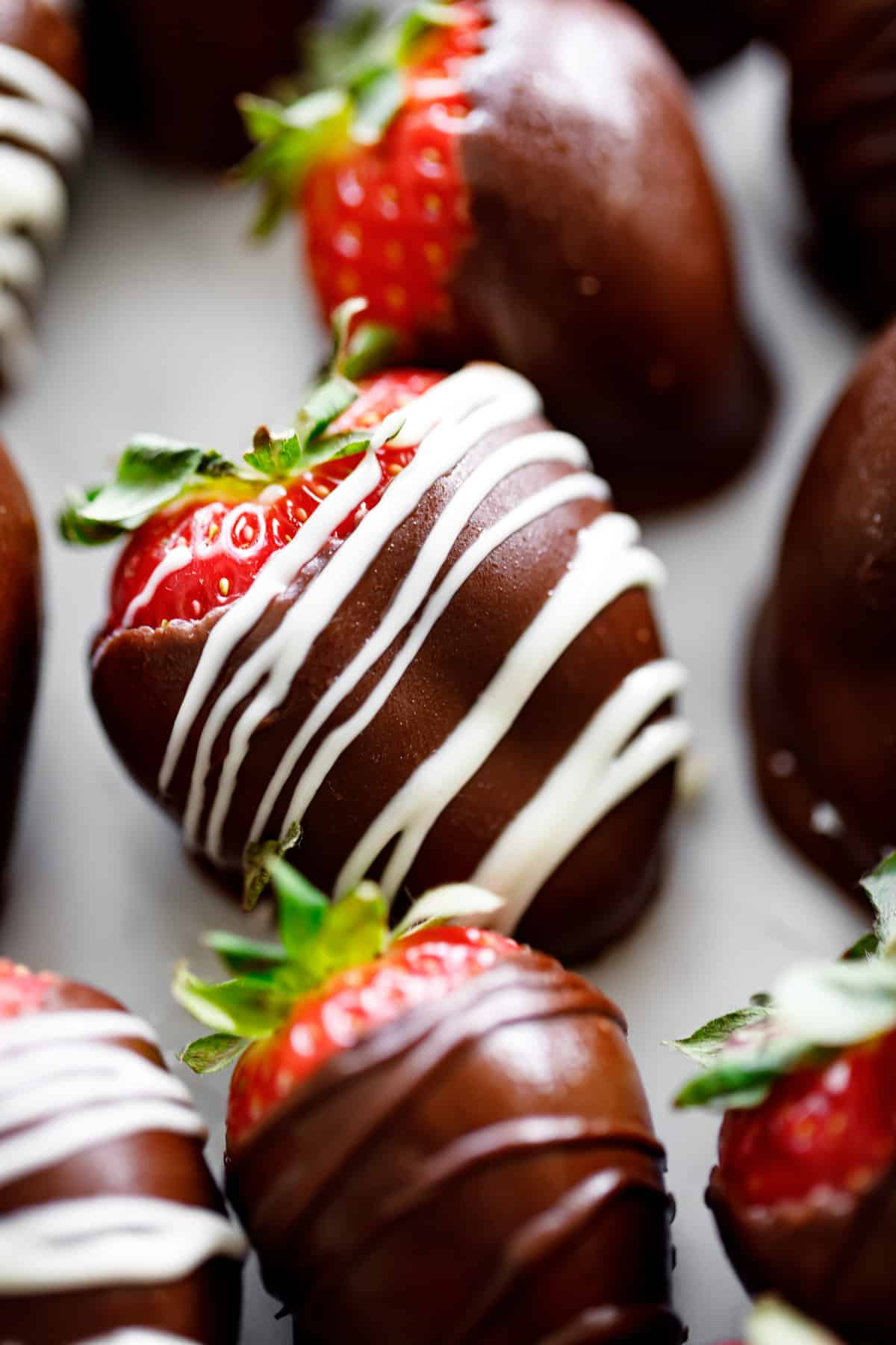 A close up photograph of a chocolate covered strawberry.