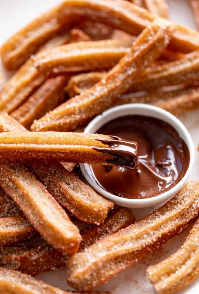 Churros dipped in chocolate sauce | cafedelites.com
