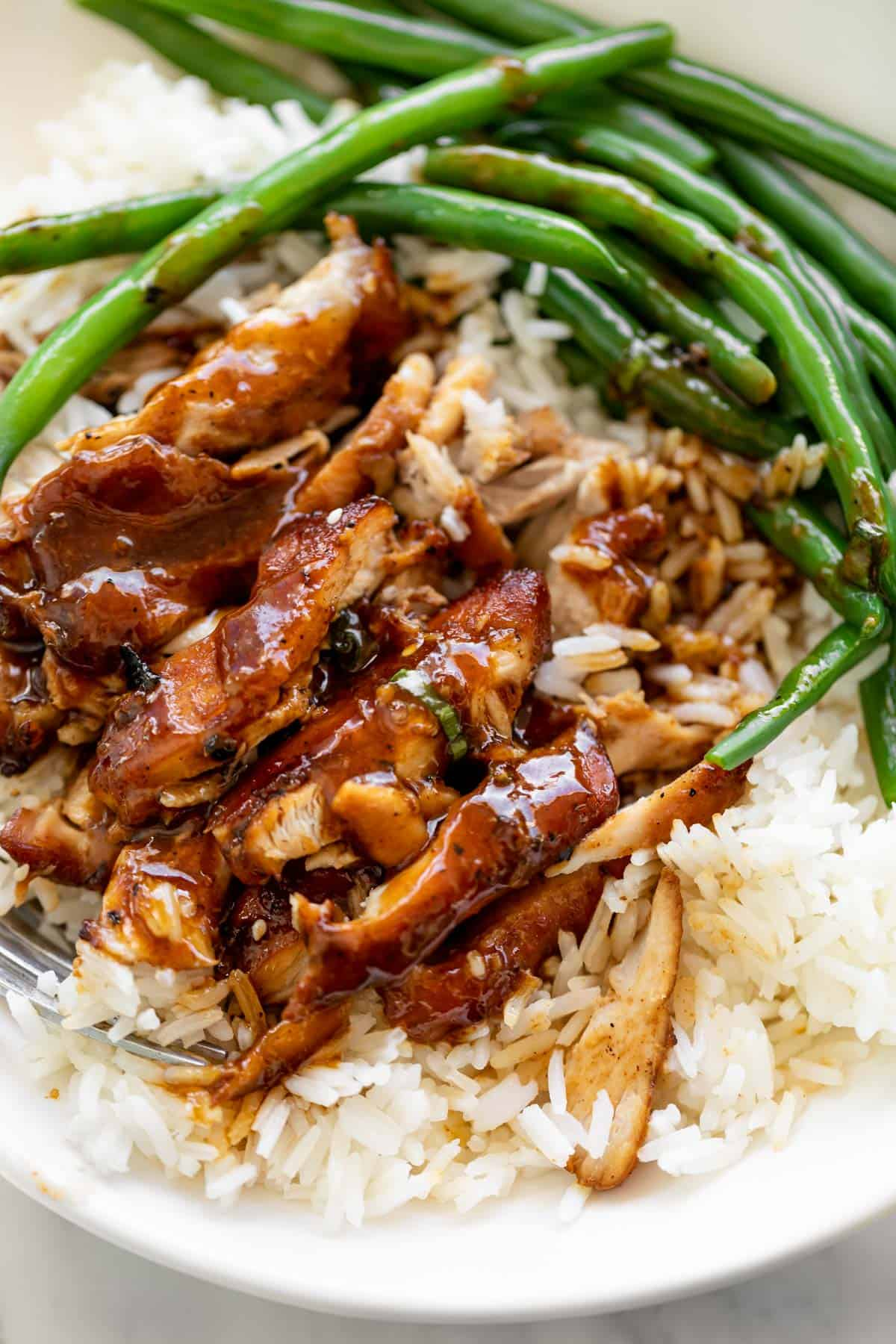 Serving suggestion: Slow cooked honey garlic chicken sits on top of plain white rice in a white bowl with sautéed green beans.