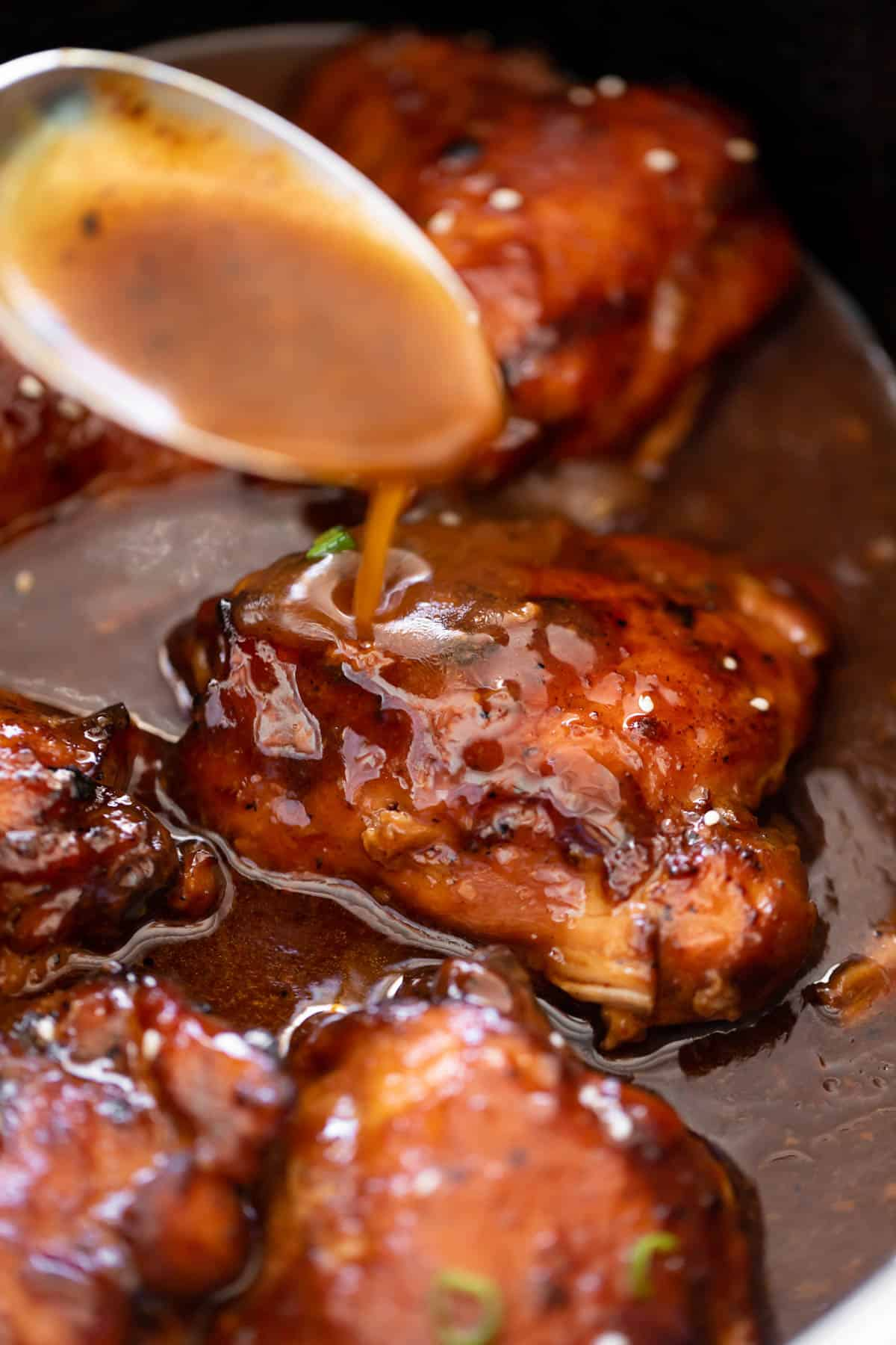 Slow Cooker Honey Garlic Chicken drizzled with honey garlic sauce in a slow cooker bowl | cafedelites.com