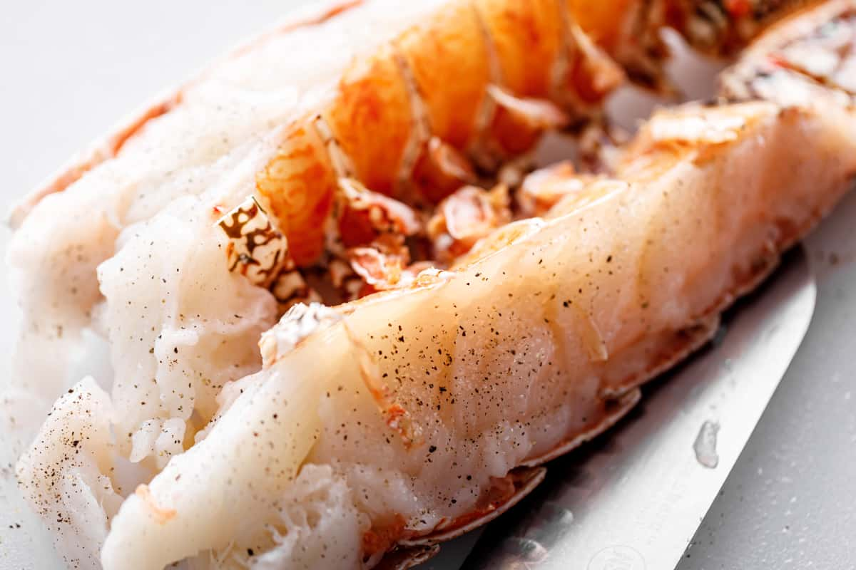 Raw lobster tail cut in half lengthways and seasoned with salt and pepper, ready for grilling.