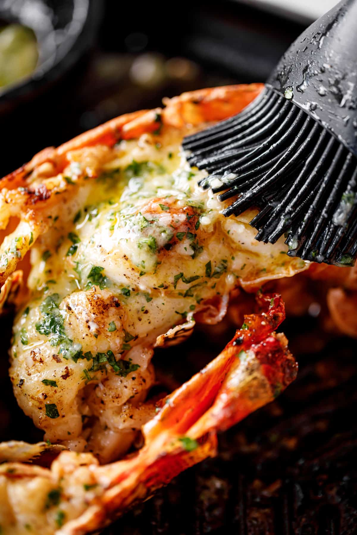 Grilled Lobster Tails brushed with melted garlic herb butter on a black grill pan | cafedelites.com