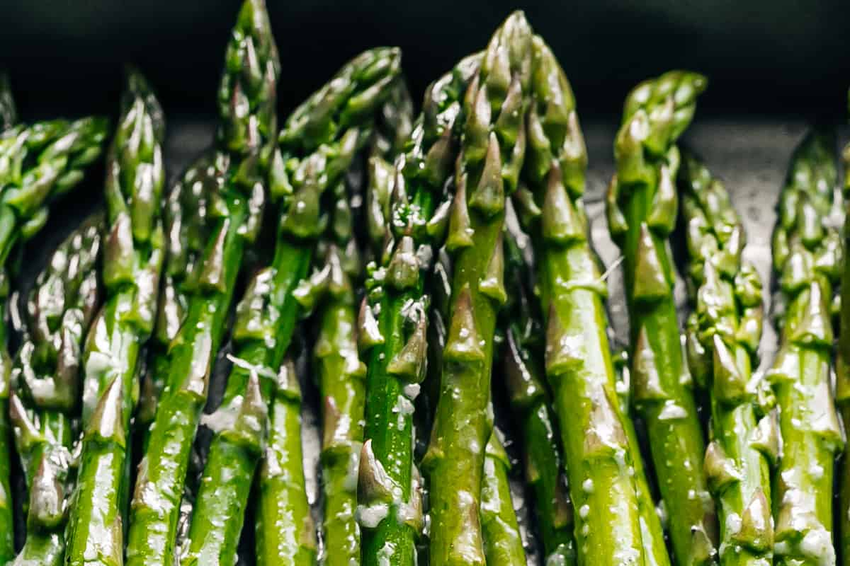 A bunch of garlic and oil coated asparagus spears on a dark grey baking sheet