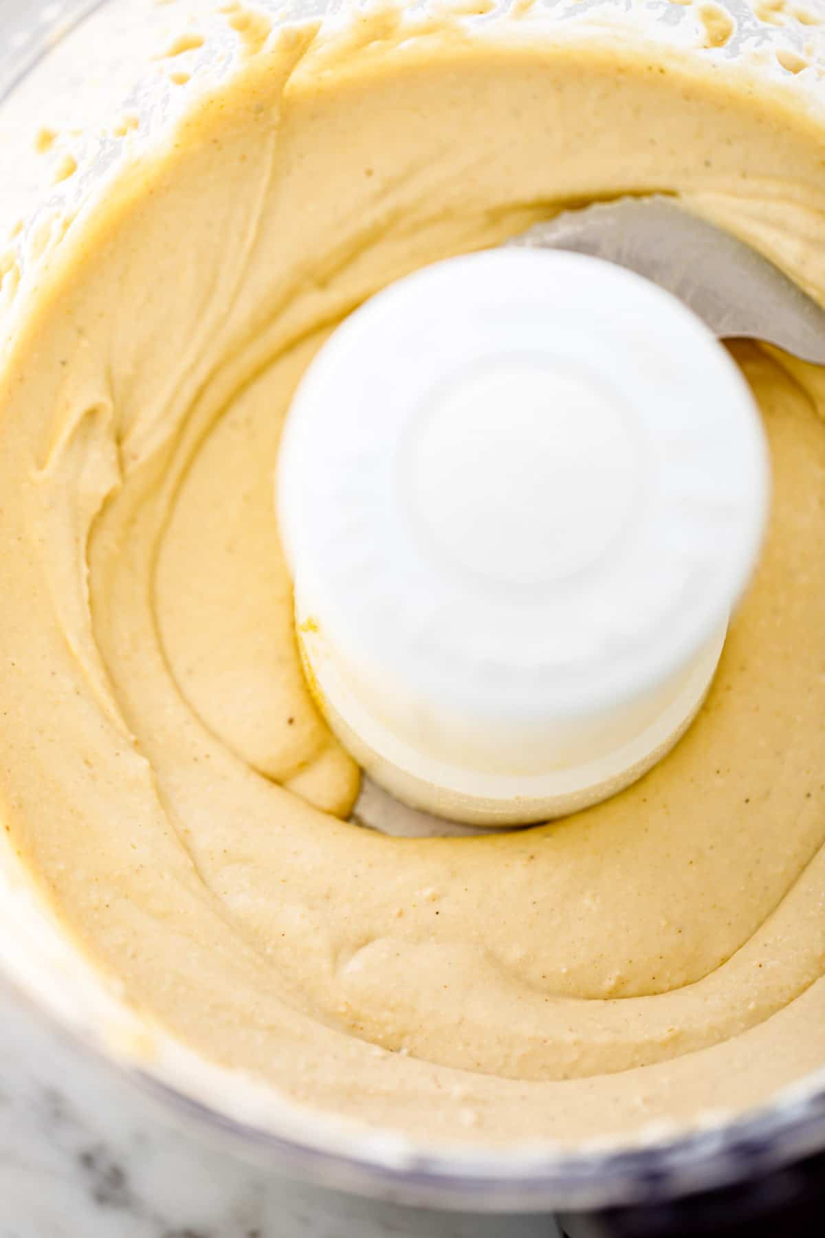 Hummus processed in a food processor bowl ready to be blended.