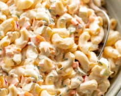 Macaroni Salad is quick to throw together and so DELICIOUS! Served in a light grey bowl on a grey linen cloth with a spoon for scooping.