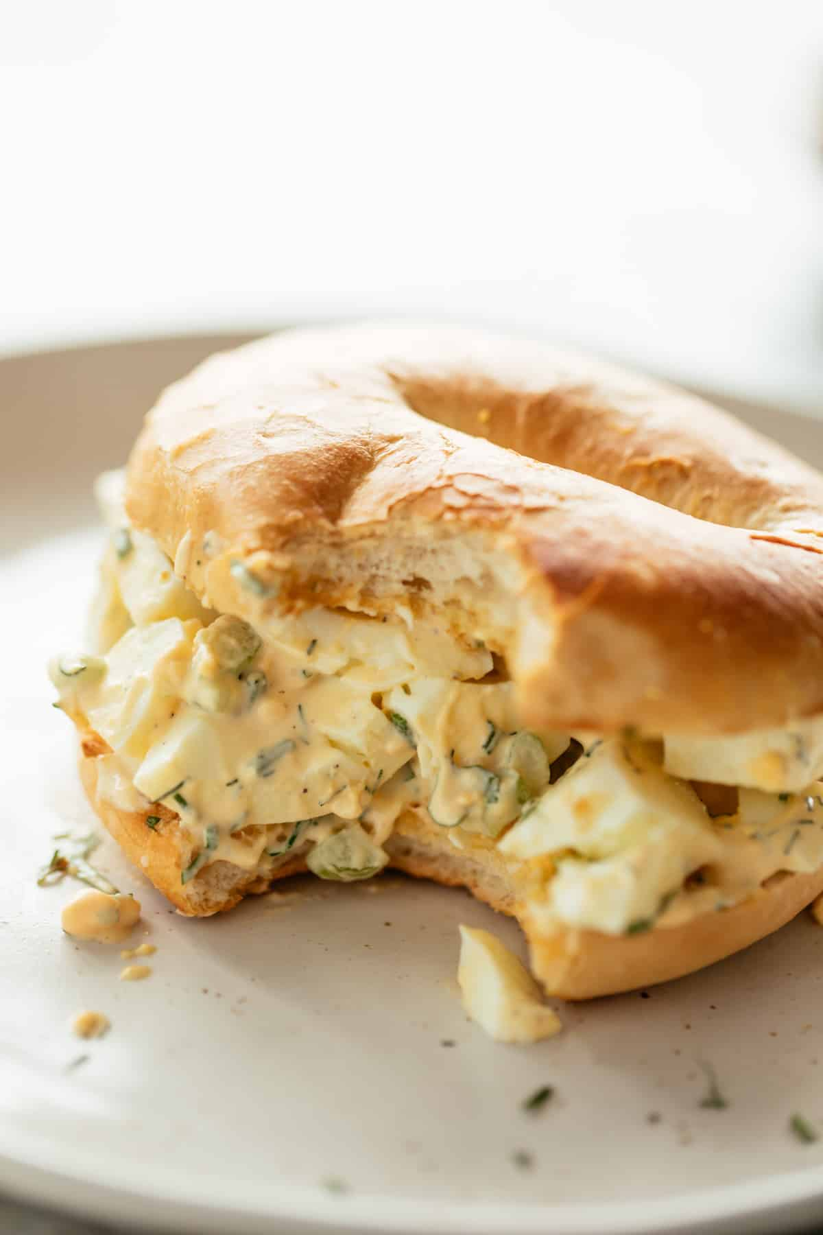 Perfect Egg Salad served sandwiched in a bagel on a white plate sprinkled with fresh dill, chives and parsley. | cafedelites.com