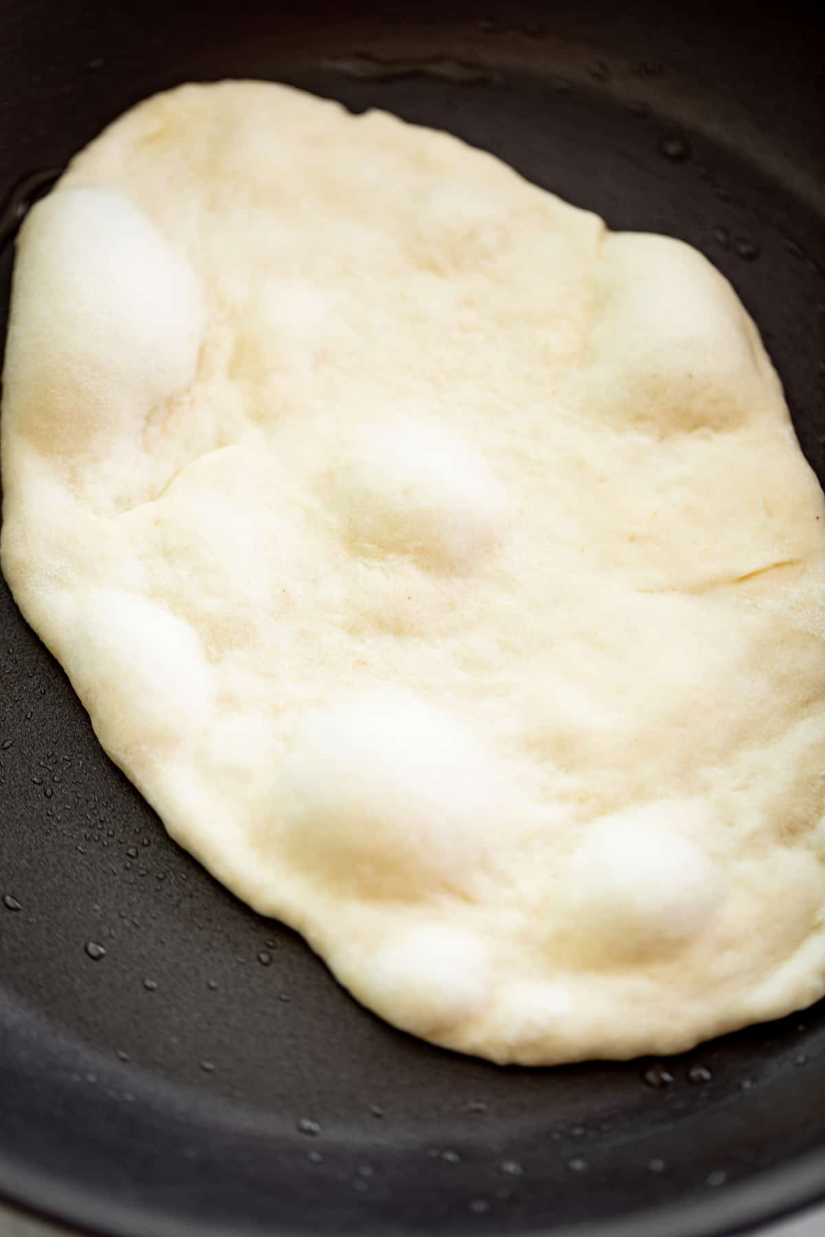 Cooking a garlic naan bread in a black skillet with a light coating of oil | cafedelites.com