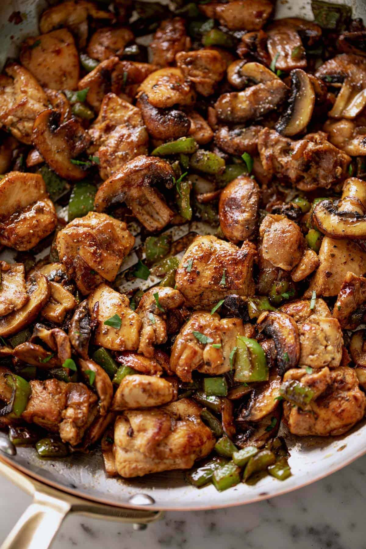 Garlic Mushroom Chicken Bites cook in no time at all! An easy dinner recipe cooked in a silver pan or skillet with a wooden spoon.   cafedelites.com
