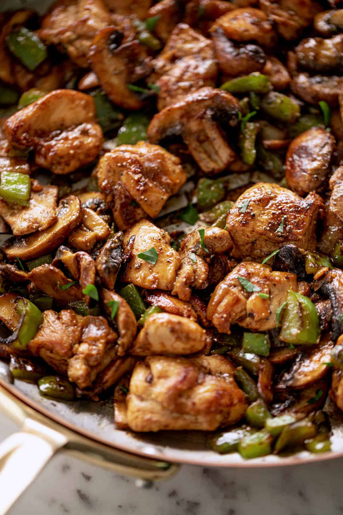 Garlic Mushroom Chicken Bites cook in no time at all! An easy dinner recipe cooked in a silver pan or skillet with a wooden spoon. | cafedelites.com