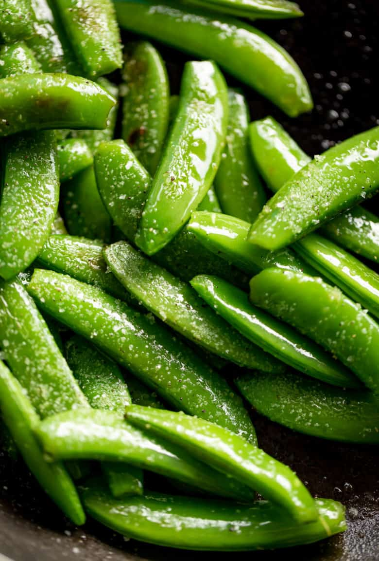 Sauteed Snap Peas in a black pan, sprinkled with coarse salt | cafedelites.com